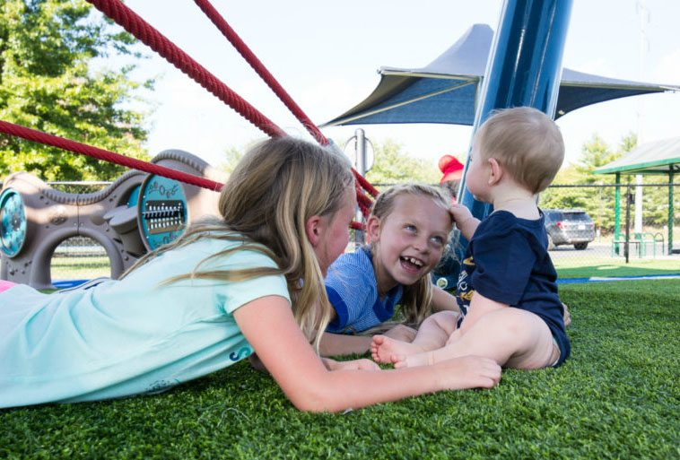 Mt. Kids playing at Mt. Ton of Fun featuring Playground Grass by ForeverLawn
