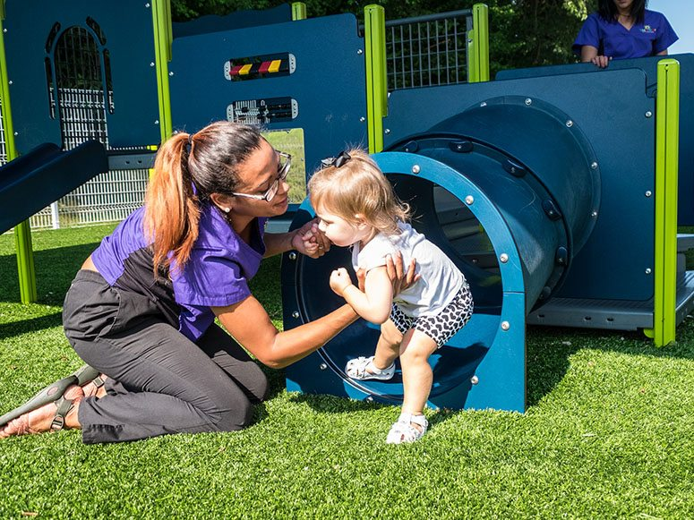 Smart Start Child Care employee and little girl playing on playground featuring Playground Grass by ForeverLawn