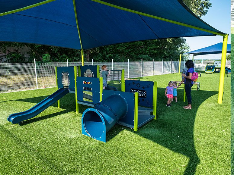 Children playing at Smart Start Child Care indoor playground featuring Playground Grass by ForeverLawn