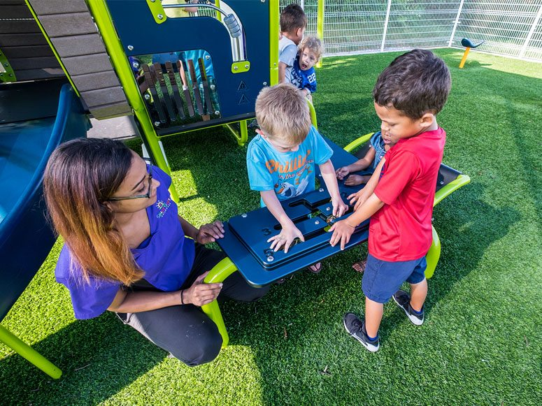 Children playing on Smart Start Child Care playground featuring Playground Grass by ForeverLawn