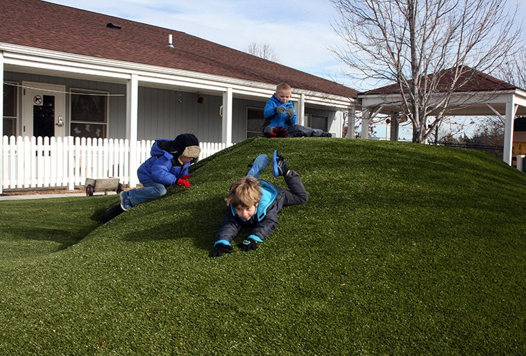 Kids playing on Playground Grass Ultra by ForeverLawn at Security Benefit Academy child care center in Topeka, Kansas