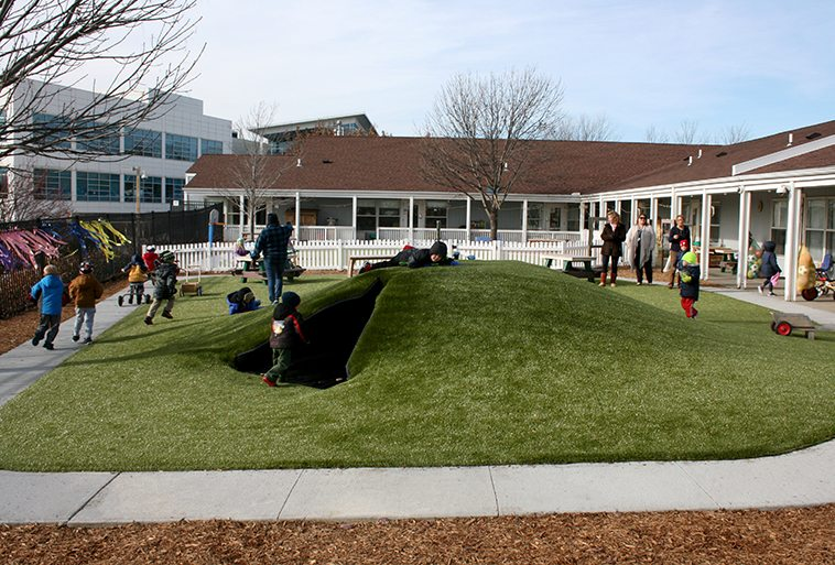 Kids playing on play mounds covered in Playground Grass Ultra by ForeverLawn at Security Benefit Academy in Topeka, Kansas
