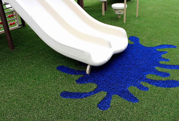 Slides on playground at Primrose School of Hillsboro featuring Playground Grass Extreme with colorful design installed by ForeverLawn of Puget Sound