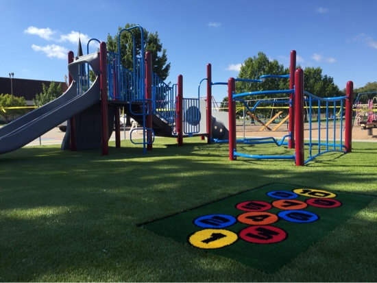 Playground at Holy Cross in Hutchinson, Kansas, featuring Playground Grass synthetic turf by ForeverLawn