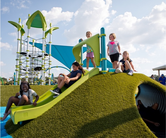 Carrollwood Village Park featuring a PlayMound™ covered in Playground Grass synthetic turf by ForeverLawn
