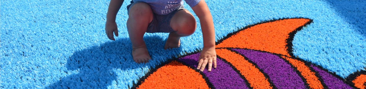 Little boy looking at fish Funsert on playground created with Playground Grass synthetic turf